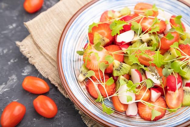 Вегетарианский салат из фруктов и овощей из клубники, киви, помидоров, ростков микрозелени на черной бетонной поверхности и льняной ткани