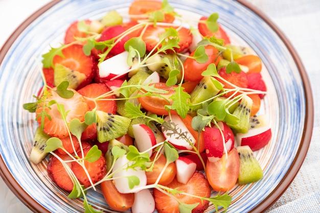 Вегетарианский салат из фруктов и овощей из клубники, киви, помидоров, ростков микрозелени на белом фоне бетона и льняной ткани.