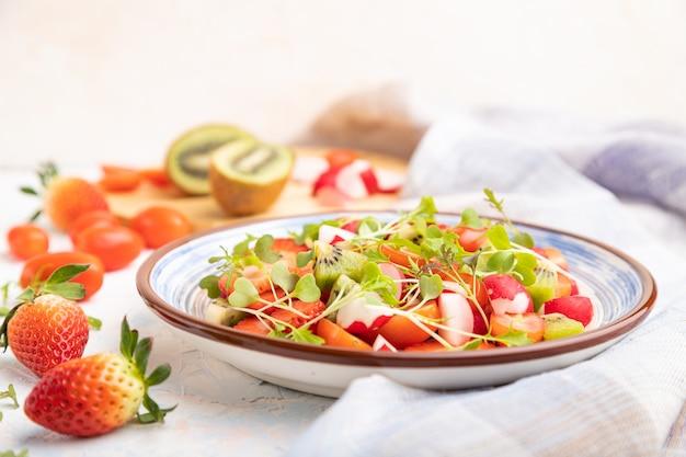 Вегетарианский салат из фруктов и овощей из клубники, киви, помидоров, ростков микрозелени на белой бетонной поверхности и льняной ткани