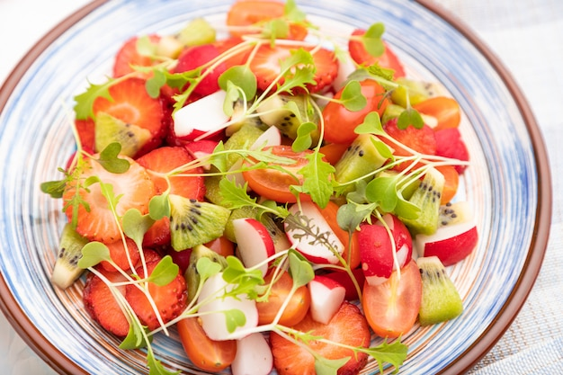 Vegetarian fruits and vegetables salad of strawberry, kiwi, tomatoes, microgreen sprouts on white concrete background and linen textile.