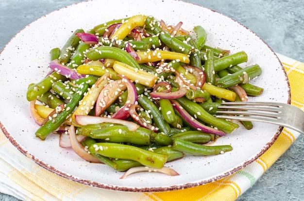 Вегетарианское блюдо из стручков зеленой фасоли с красным маринованным луком и кунжутом. студийное фото.