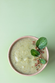 Vegetarian green cream soup in craft container for take away food. delivery concept.