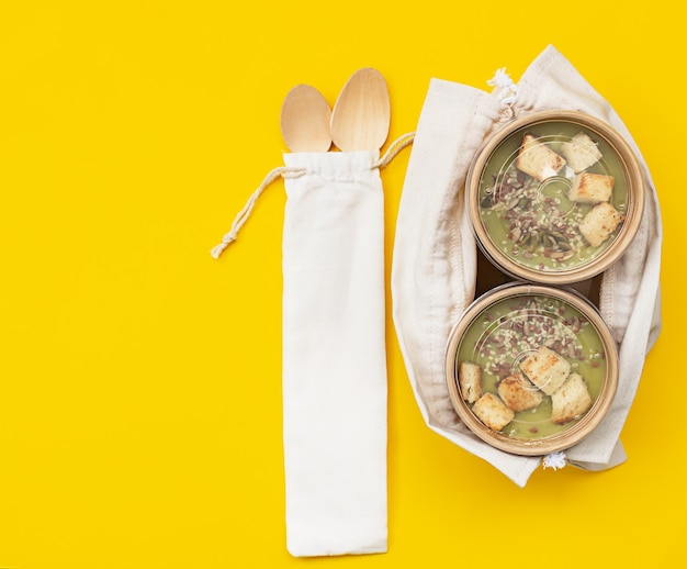 Vegetarian green cream soup in craft container for takeaway food