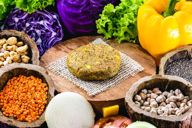 Vegetarian hamburger, made with soy and grains, with vegetables around