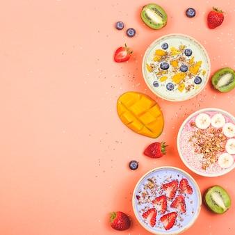 밝은 분홍색 테이블에 성냥과 딸기와 멀티 컬러 스무디로 만든 채식 건강 식품.
