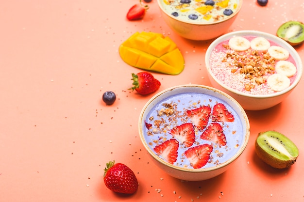 Vegetarian healthy food made from multi-colored smoothies with matches and berries on a bright pink table