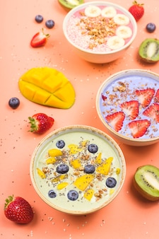 Vegetarian healthy food made from multi-colored smoothies with matches and berries on a bright pink table.