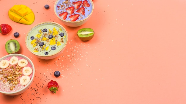 Vegetarian healthy food made from multi-colored smoothies with matches and berries on a bright pinktable.