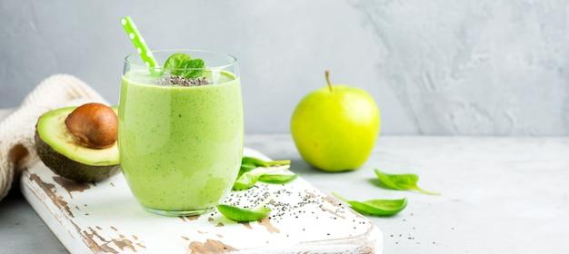 회색 콘크리트 배경에 유리에 아보카도, 시금치 잎, 사과, 치아 씨로 만든 건강한 녹색 스무디. 선택적 초점입니다. 텍스트를 위한 공간입니다. 배너.