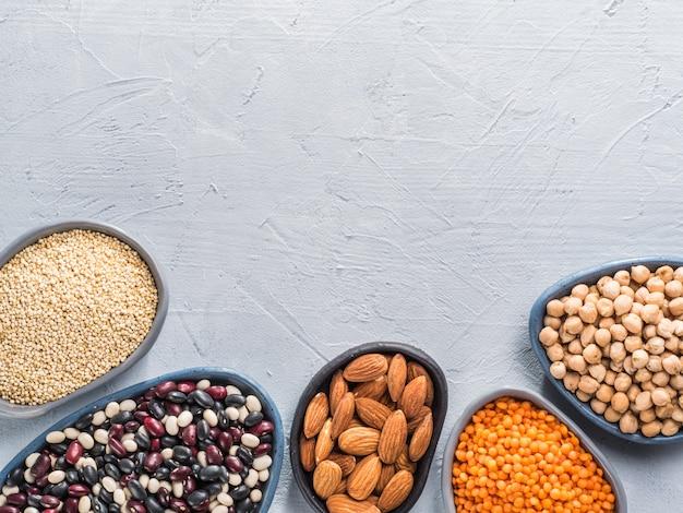 회색 콘크리트 배경의 퀴노아 치크피 아몬드 붉은 렌즈콩 혼합 콩을 단백질 개념의 완전채식 소스로 채식주의 건강한 단백질 공급원은 상단 보기 또는 평평한 복사 공간을 닫습니다