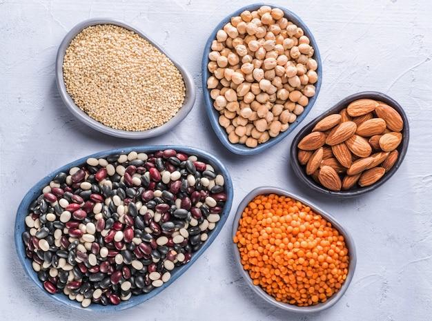 회색 콘크리트 배경에 있는 채식주의 건강한 단백질 공급원 퀴노아 치크피 아몬드 붉은 렌즈콩은 단백질 개념의 완전 채식 공급원으로 상위 뷰 또는 평평한 평지를 닫습니다.