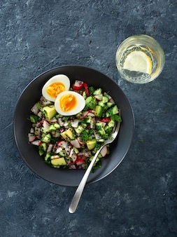 Vegetarian healthy salad with cucumber, radish, avocado and quinoa