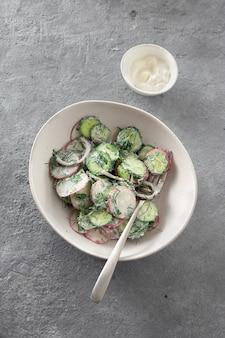 Vegetarian healthy summer salad with cucumber, radish and natural yoghurt