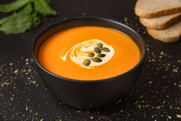 ベジタリアンの自家製カボチャとニンジンのスープ、クリームとカボチャの種