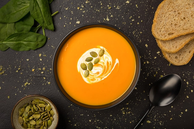 Vegetarian homemade pumpkin and carrot soup with cream and bread flat lay on dark background