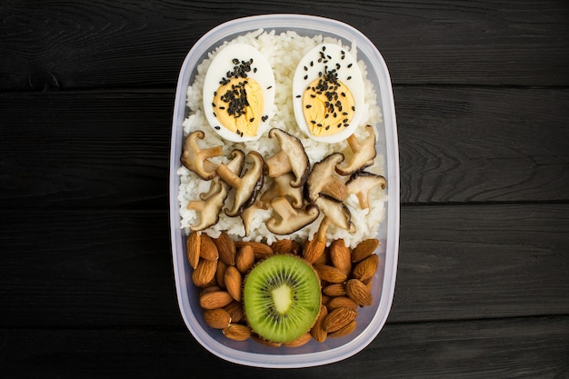 Вегетарианский обед в коробке на черном деревянном фоне. вид сверху. копировать пространство. здоровые пищевые ингредиенты.