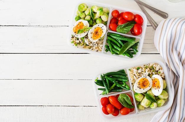 卵、芽キャベツ、インゲン、トマトが入ったベジタリアンミールの準備容器。ランチボックスで夕食。上面図。フラットレイ