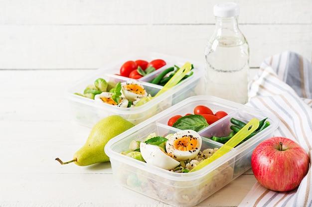 Contenitori per preparazione pasti vegetariani con uova, cavoletti di bruxelles, fagiolini e pomodoro. cena a pranzo