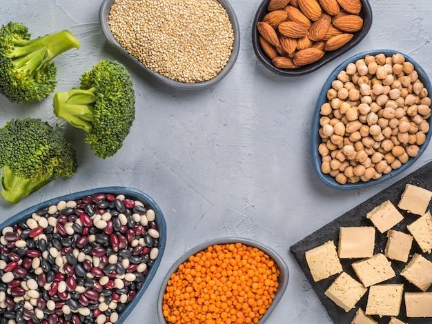채식주의자 또는 채식주의자 건강에 좋은 단백질 공급원은 회색 콘크리트 배경에 있는 퀴노아 치크피 아몬드 붉은 렌즈콩 혼합 콩 브로콜리 두부를 상위 뷰 또는 평평한 복사 공간을 닫습니다.