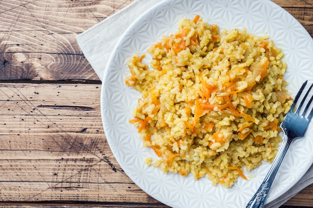 Vegetarian oriental pilaf with rice and vegetables on a wooden table.
