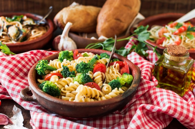 Vegetarian pasta fusilli with tomato and broccoli in the earthenware on tablecloth