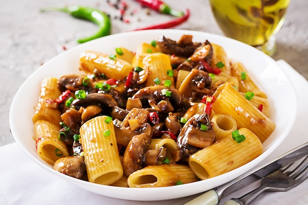 Vegetarian pasta  rigatoni with mushrooms and chilli peppers in white bowl