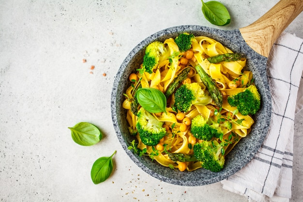 Vegetarian pasta with broccoli, asparagus and chickpeas in pan