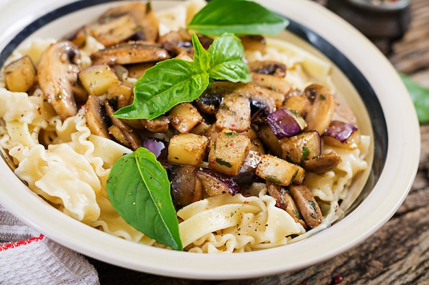 Vegetarian pasta with mushrooms and aubergines, eggplants. italian food. vegan meal.