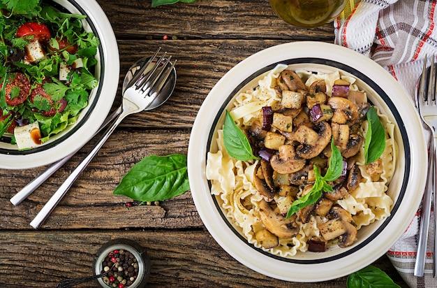 Vegetarian pasta with mushrooms and aubergines, eggplants and salad. italian food. vegan meal. top view. flat lay.