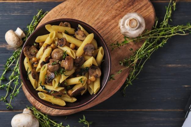 Вегетарианская паста с грибами, нутом, шпинатом, специями и зеленью. итальянская паста в миске на старом деревянном столе. вид сверху.