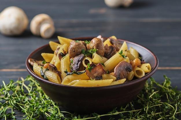 Вегетарианская паста с грибами, нутом, шпинатом, специями и зеленью. итальянская паста в миске на старом деревянном столе.