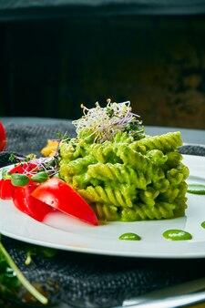 マイクログリーンのベジタリアンペストパスタ。白い皿と灰色の布にトマトとグリーンソースのパスタ。健康的でバランスの取れた料理。ビューを閉じます。