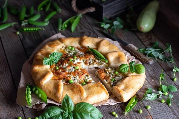 Вегетарианский пирог с цукини и зеленым горошком на деревянном столе