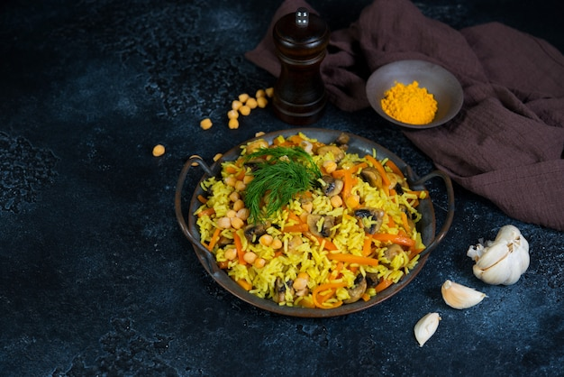 Vegetarian pilaf with mushrooms, vegetables and chickpeas on a black wall. horizontal photo with copy space.
