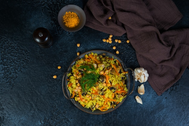 Vegetarian pilaf with mushrooms, vegetables and chickpeas in the center on a black wall. horizontal photo. top view.