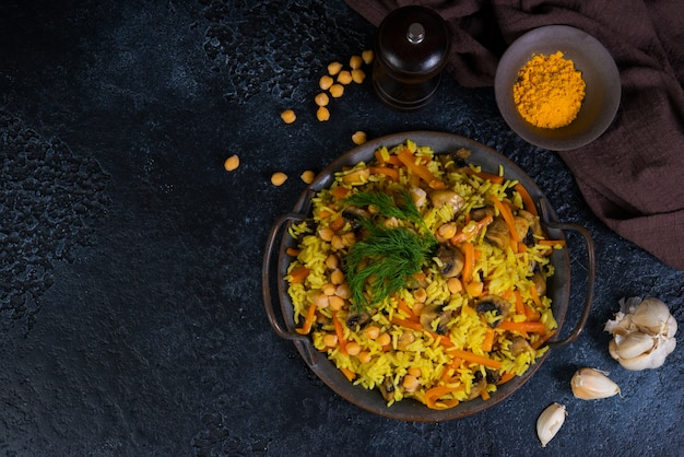Vegetarian pilaf with mushrooms, vegetables and chickpeas on the right on a black wall. horizontal photo with copy space. top view