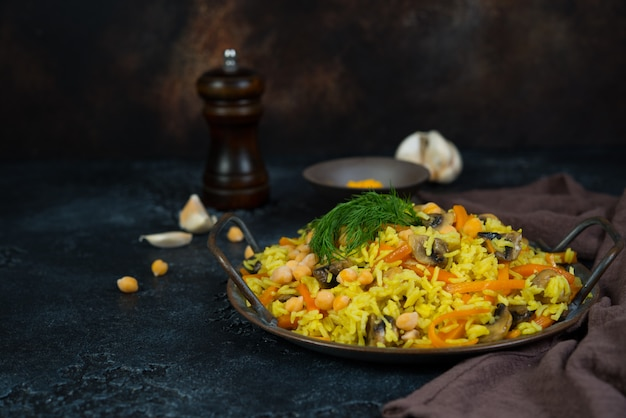 Vegetarian pilaf with mushrooms, vegetables and chickpeas on the right on a black wall. horizontal photo with copy space.