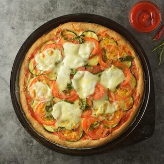 통 곡물 반죽, 호박, 토마토 및 모짜렐라로 만든 채식 피자.
