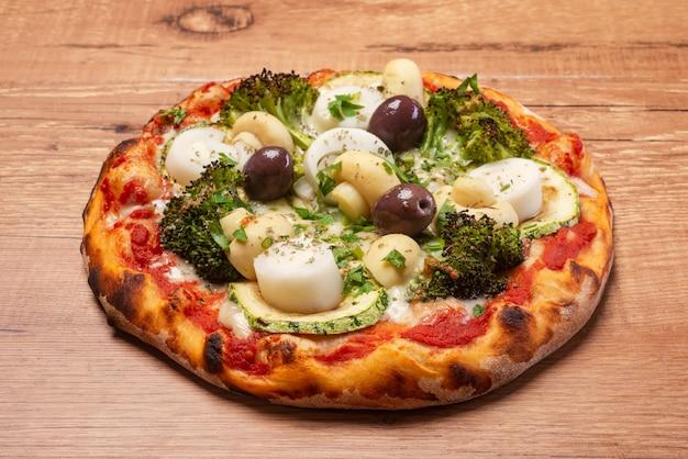 Вегетарианская пицца с брокколи, пальмовыми сердцами, оливками и цукини подается на деревенском деревянном столе.