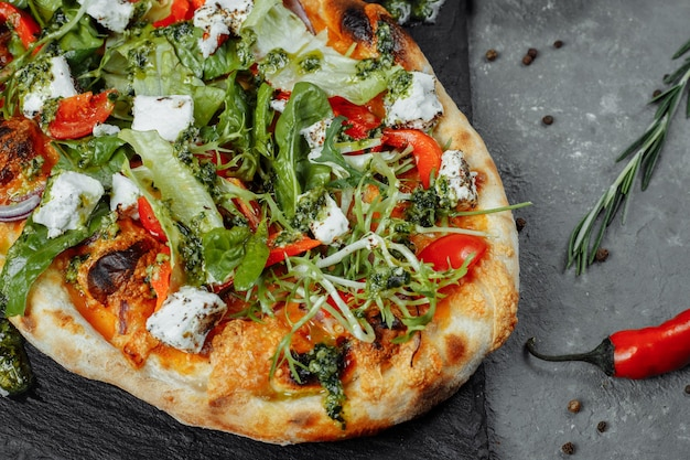 Vegetarian pizza with cheese tomatoes and greens.