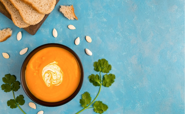 Vegetarian pumpkin and carrot soup with cream in black bowl flat lay