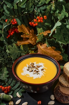 Vegetarian pumpkin soup in black bowl with cream and pumpkin seeds, close-up, selective focus on soup and seeds. on a dark wooden table, plate of soup stands surrounded by autumn oak and rowan leaves