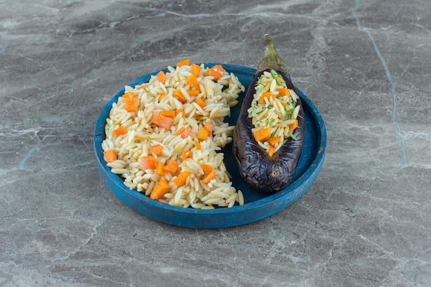 Вегетарианский рис в баклажанах, на тарелке, на мраморном столе.