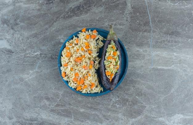 Вегетарианский рис в баклажанах, на тарелке, на мраморном столе. Бесплатные Фотографии