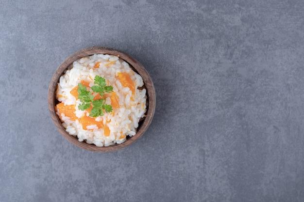 Вегетарианский рис в миске на мраморной поверхности.