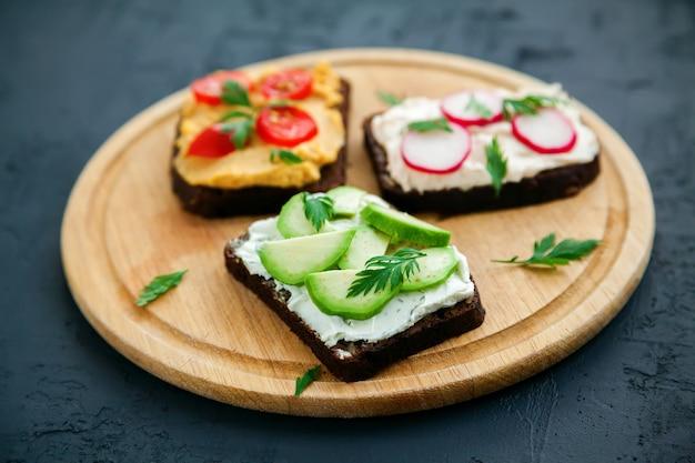 Вегетарианские гренки из ржаного хлеба с творогом, хумусом, авокадо, редисом и помидорами на деревянной доске, черная поверхность