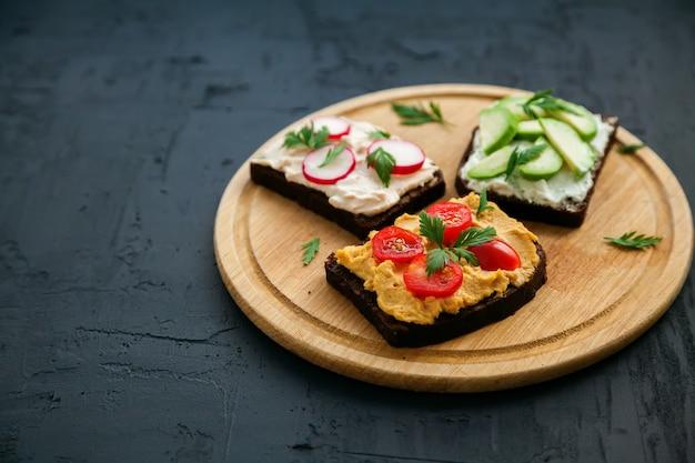 Вегетарианские гренки из ржаного хлеба с творогом, хумусом, авокадо, редисом и помидорами. деревянная доска на черной поверхности, copy-space