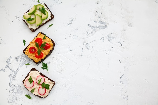 Vegetarian rye bread toasts with cottage cheese, hummus, avocado, raddish and tomato on a white background, copy-space, top view