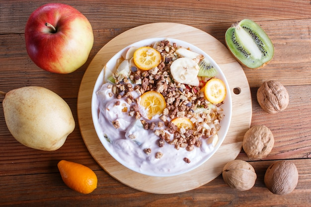 Vegetarian salad of bananas, apples, pears, kumquats, kiwi with granola and yogurt on brown wooden table.