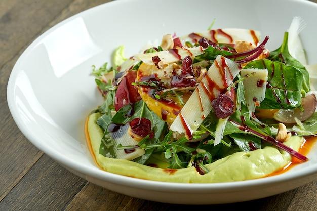Вегетарианский салат с муссом из авокадо, сыром пармезан, шпинатом, ягодным соусом и запеченными яблоками в тарелке на деревянном столе